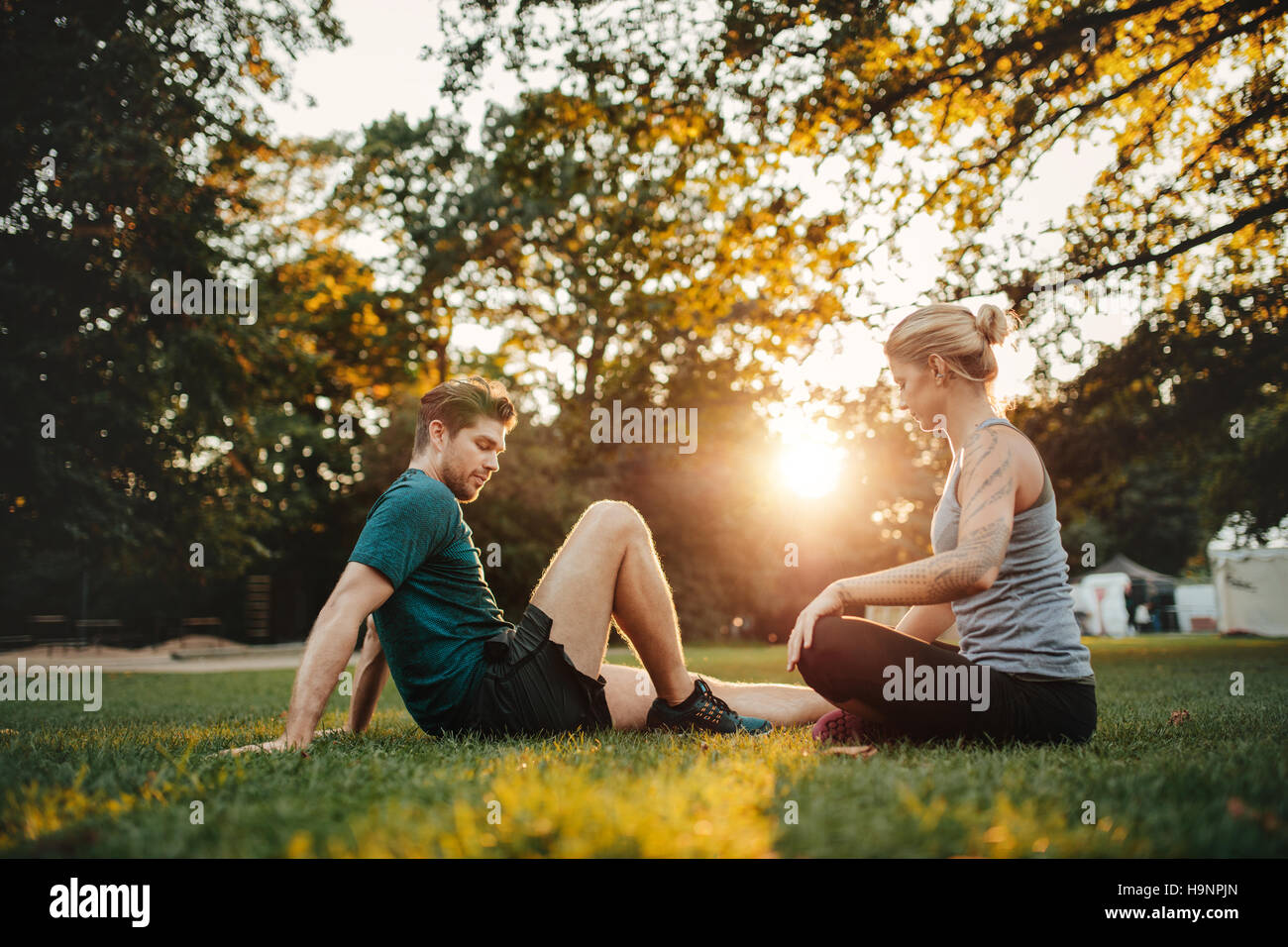 Shot of young couple sitting at park and working out. Man and woman exercising at park in morning. - Stock Image