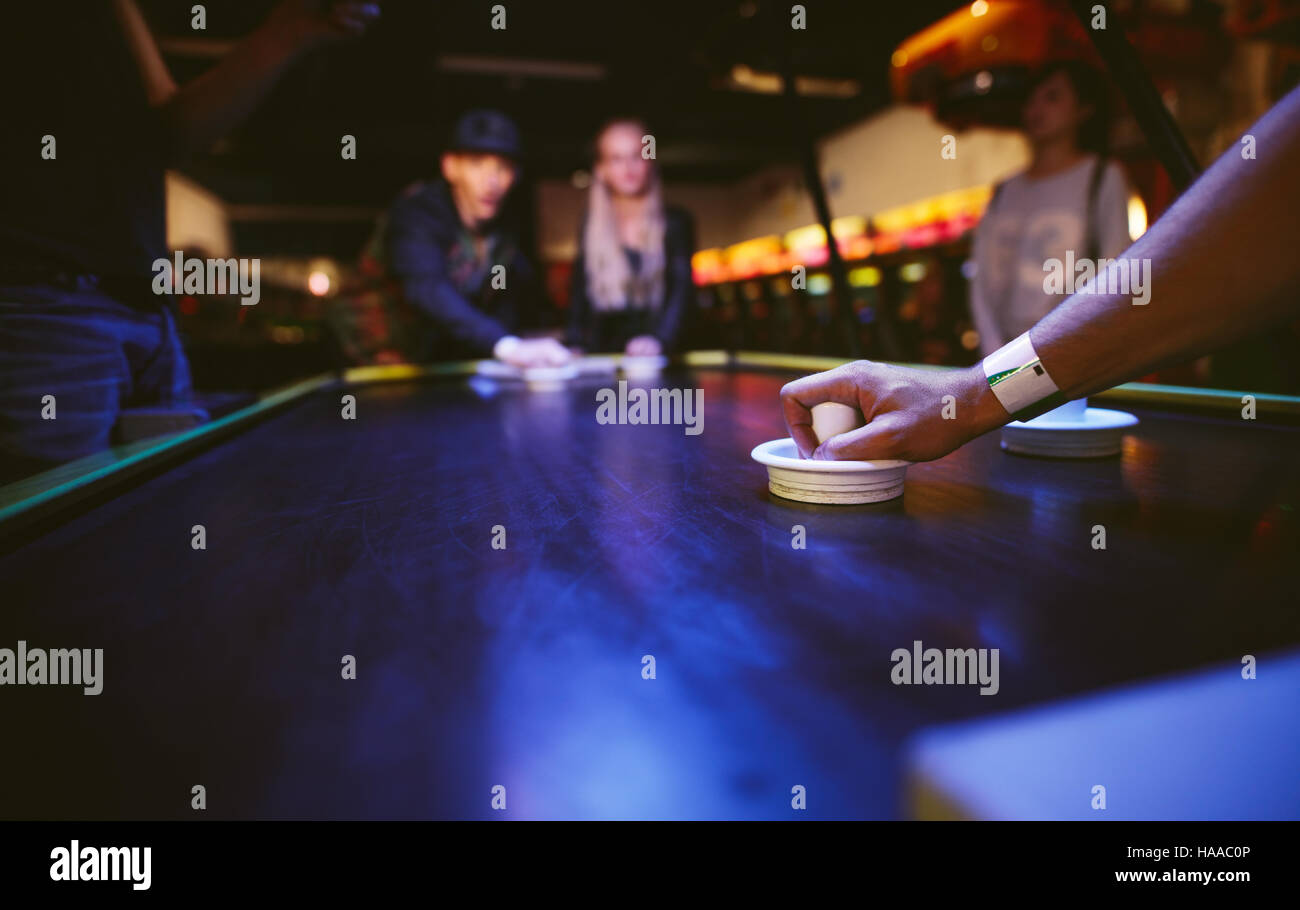 Young friends playing air hockey game at amusement park, focus on hand of man holding striker. - Stock Image