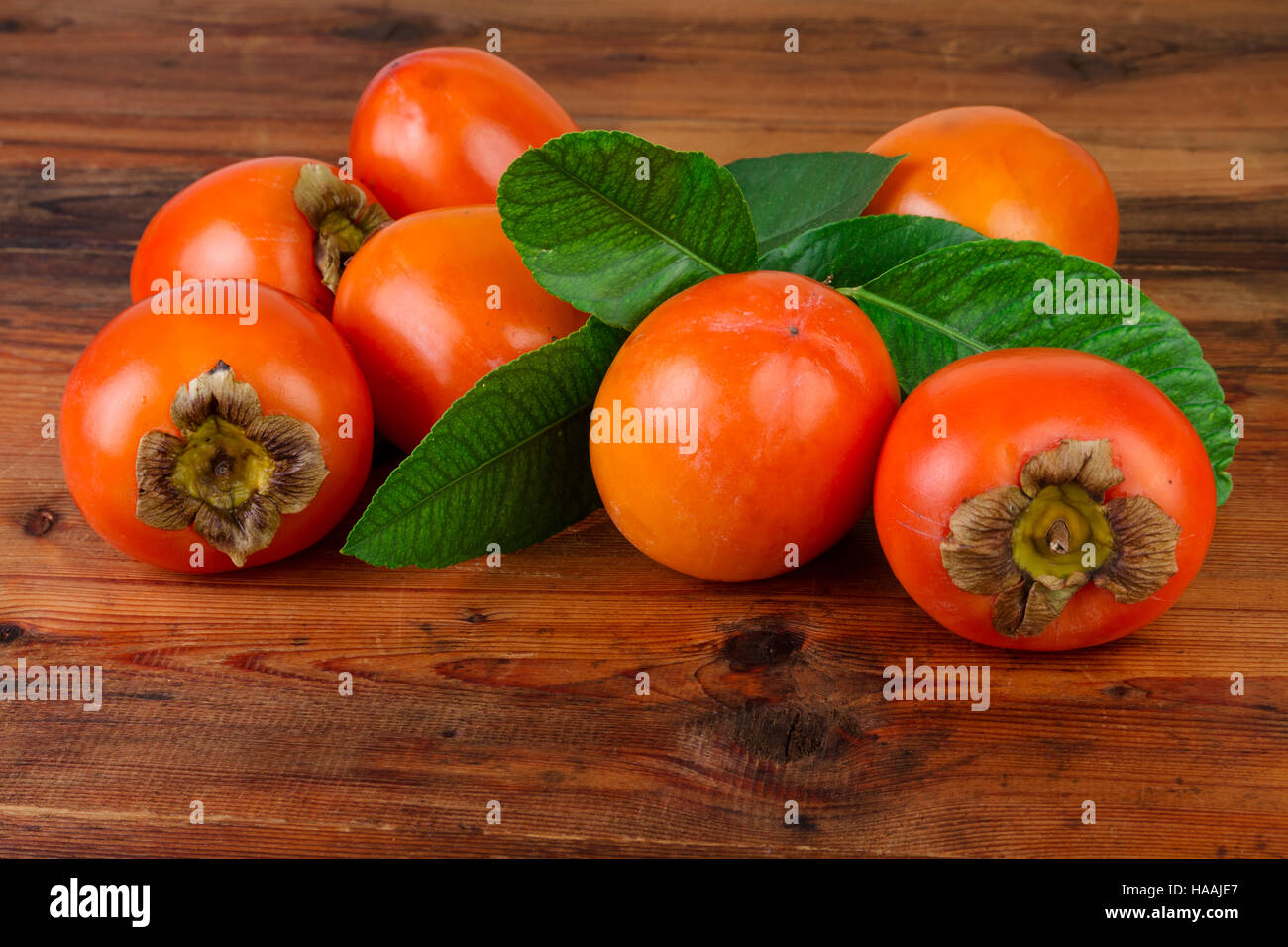 persimmon kaki fruits on wooden table - Stock Image
