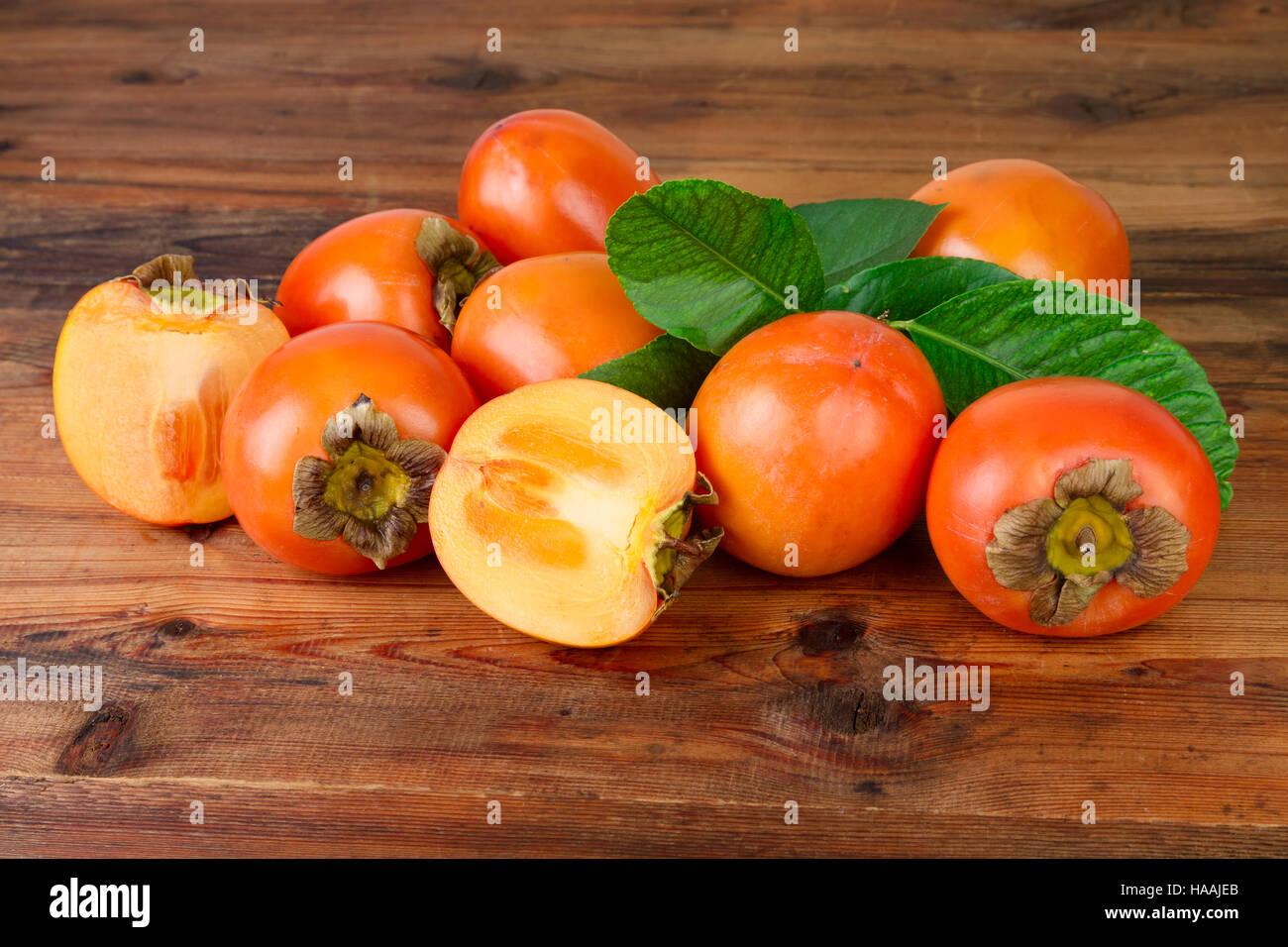 Persimmon. Kaki fruits on old wooden background. - Stock Image