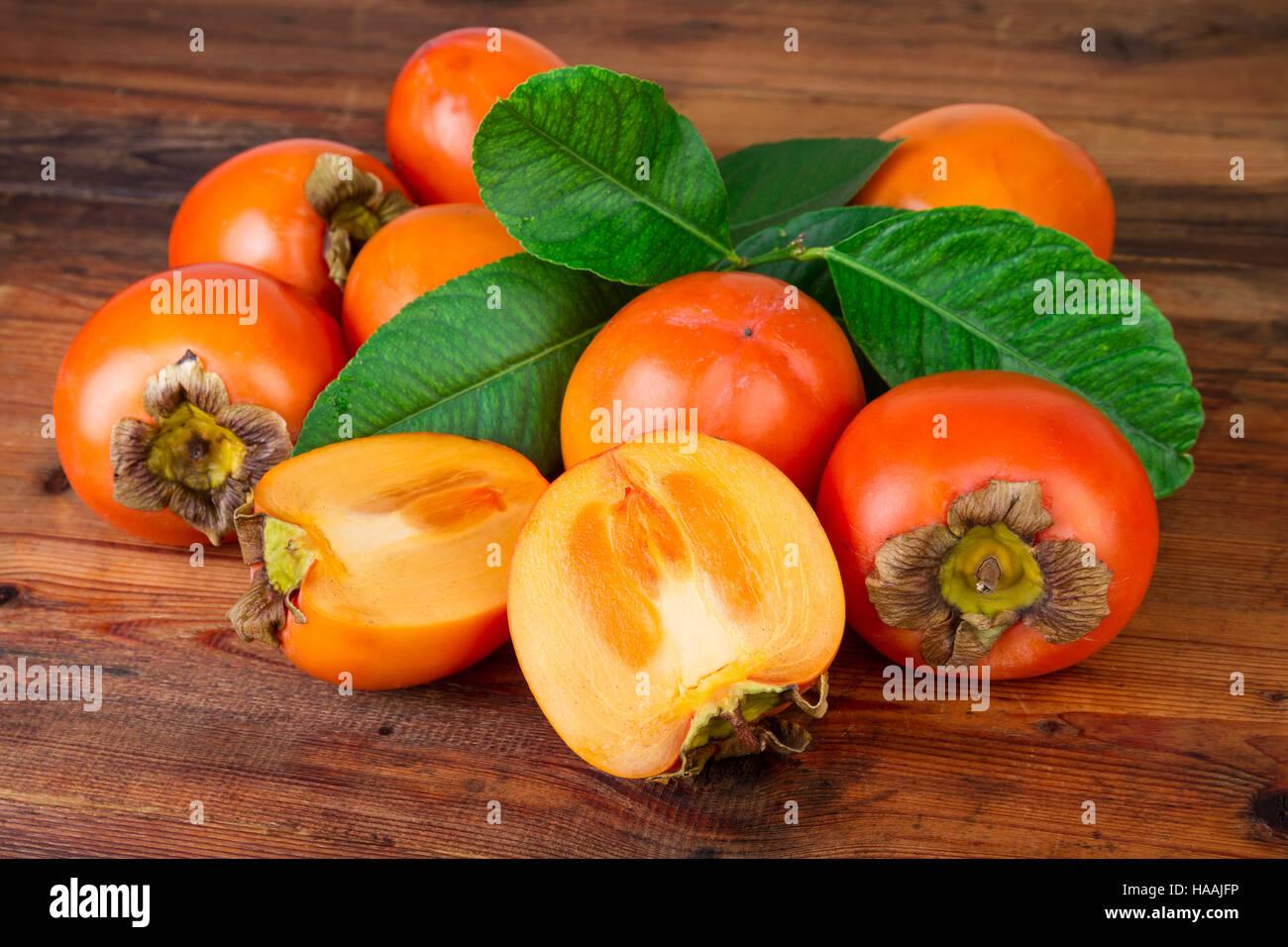 ripe persimmons kaki fruits on rustic background - Stock Image
