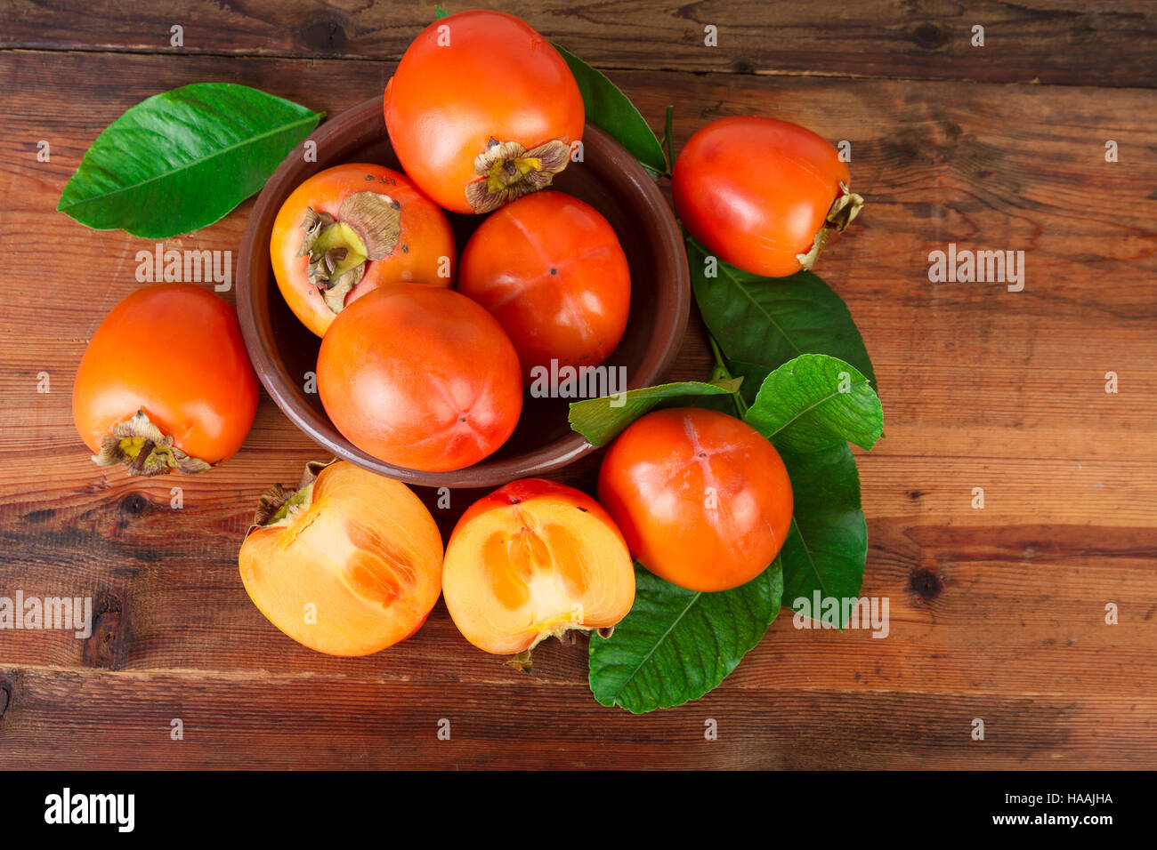 Persimmon fruits rustic background top view - Stock Image