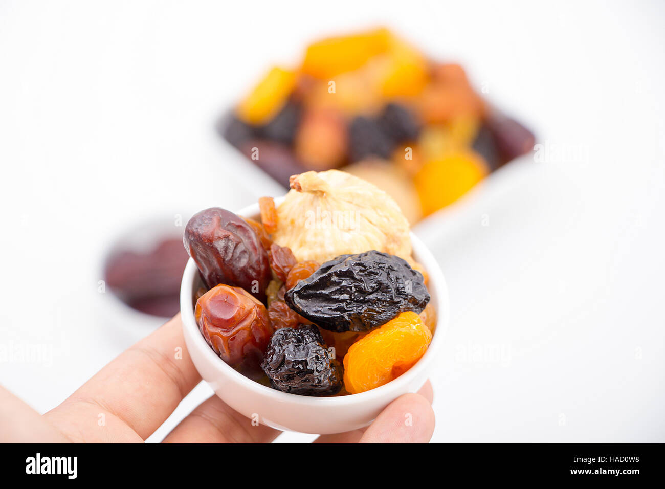 Muslim hand presenting collection of Ramadan dried fruits - Stock Image