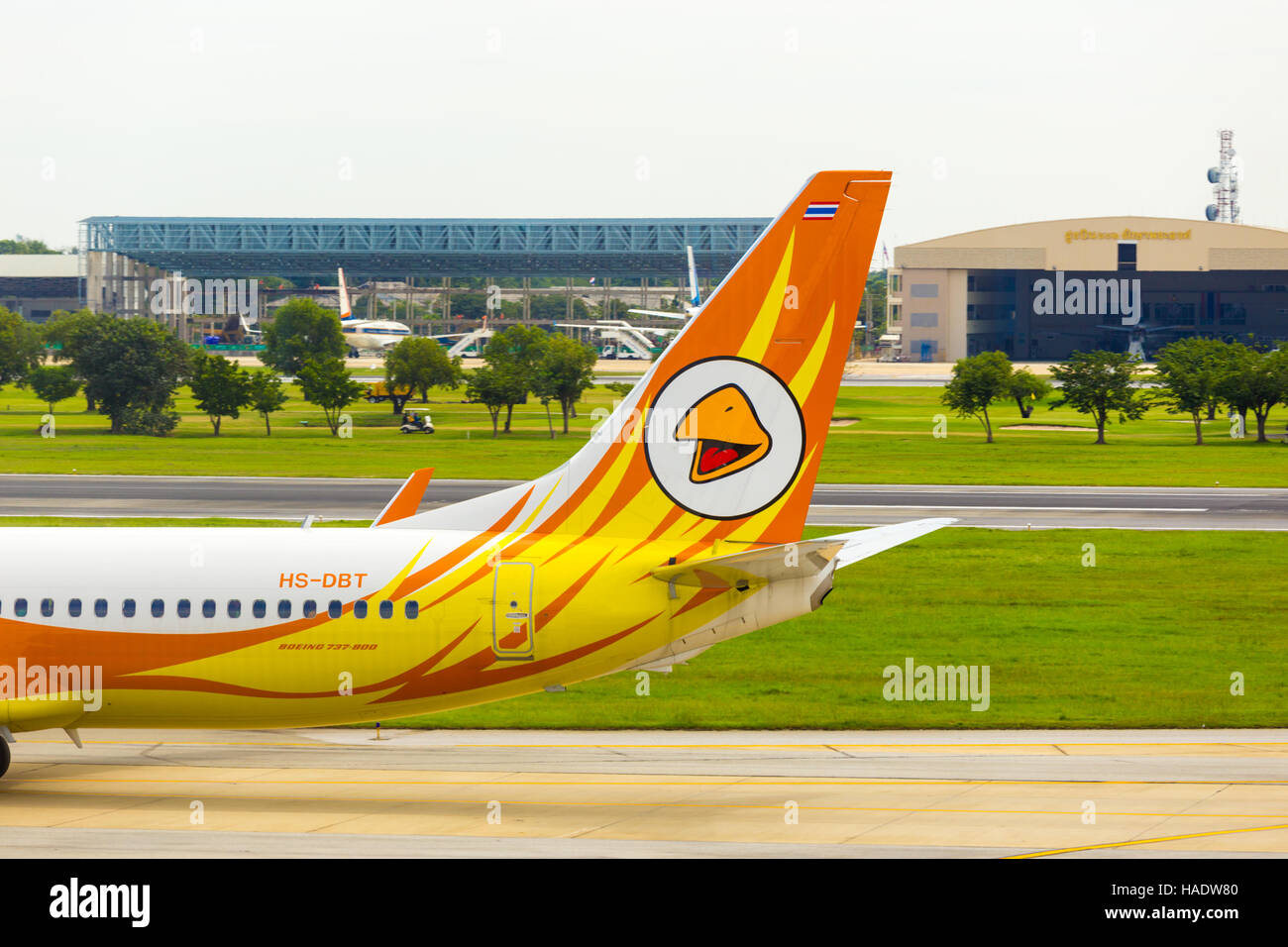 Golf course and golfers in cart visible behind the tail section and logo of low cost carrier, Nok Air airplane taxiing - Stock Image