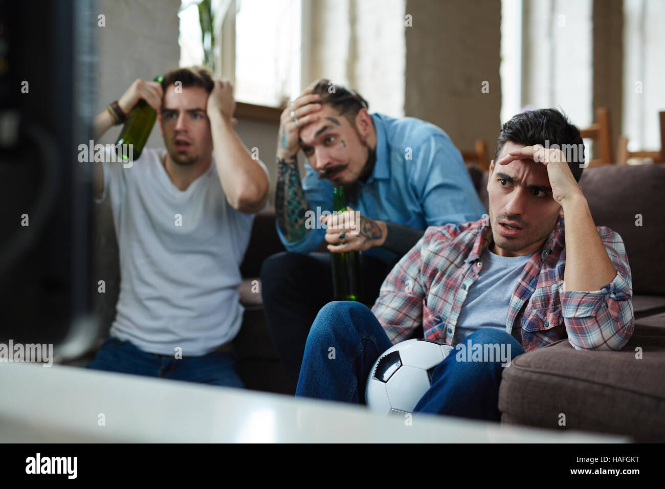 Dissatisfied guys sitting in front of tv and watching football broadcast Stock Photo