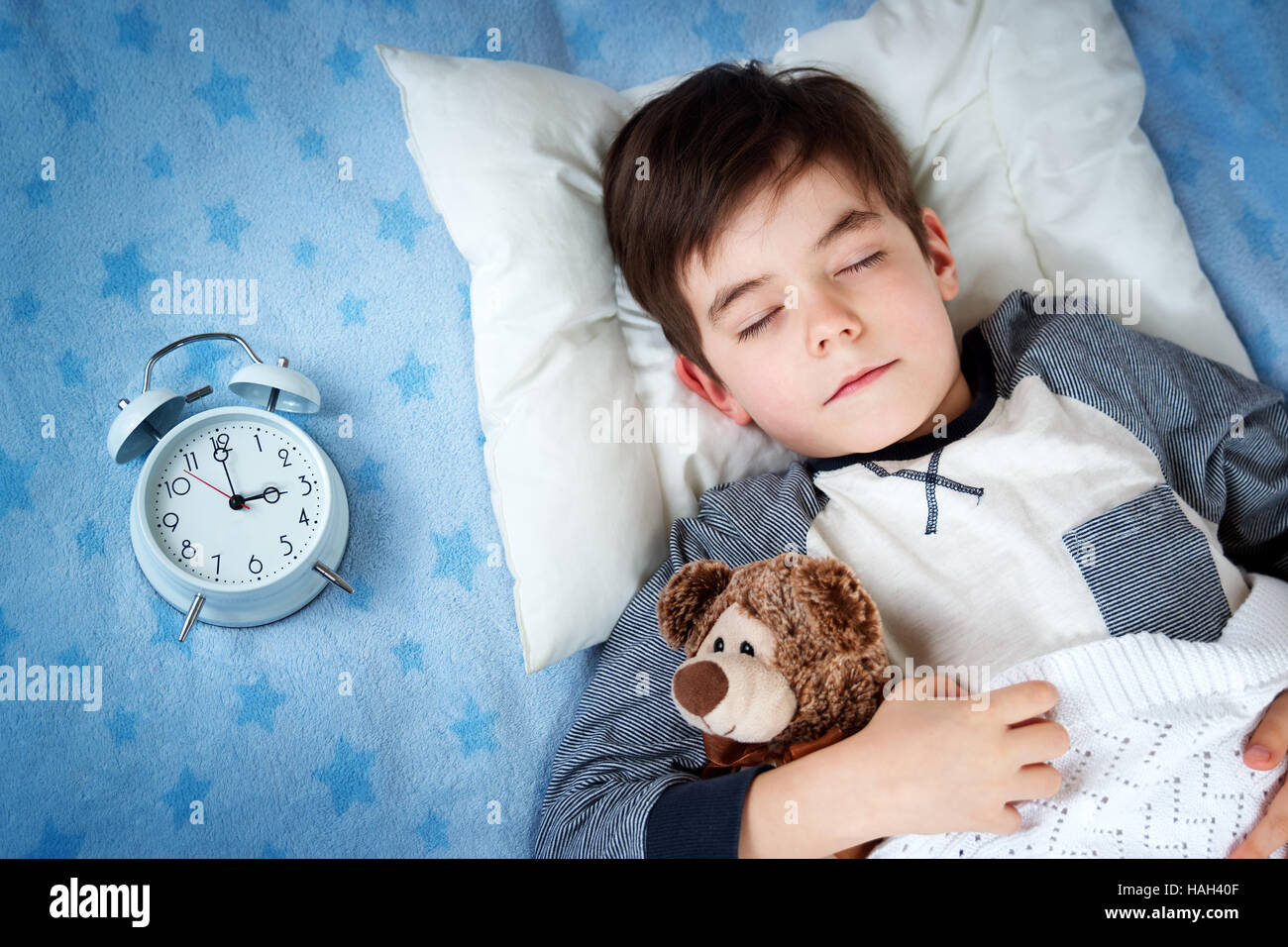 six years old child sleeping in bed with alarm clockStock Photo