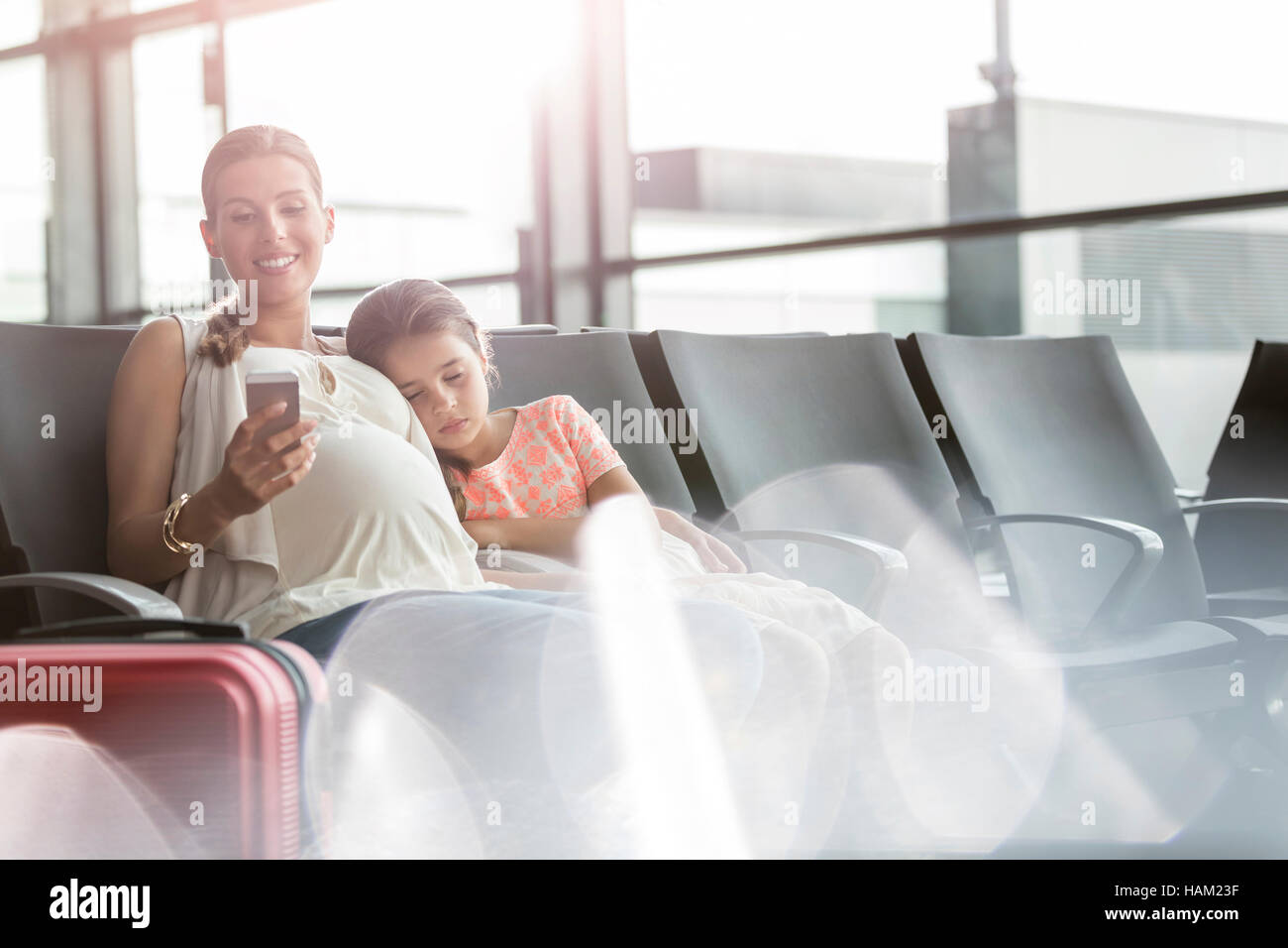 Pregnant mother with cell phone and sleeping daughter in airport departure area - Stock Image