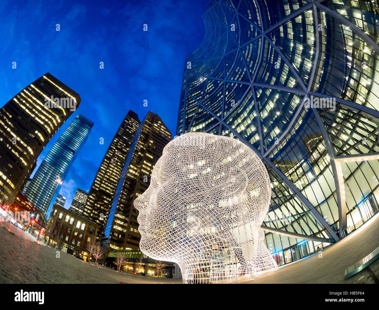 A night, fisheye view of the sculpture Wonderland by Jaume Plensa, in front of The Bow skyscraper in Calgary, Alberta, Stock Photo