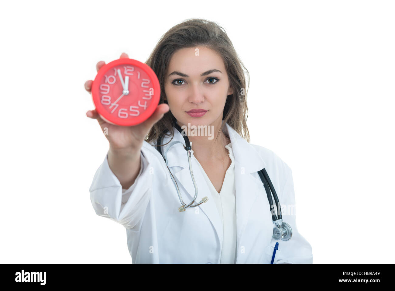 Serious female doctor holding clock. - Stock Image