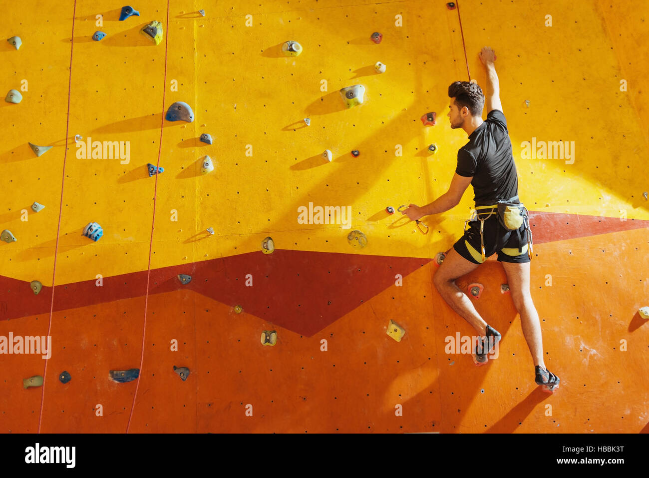 Fearless man climbing up the wall - Stock Image