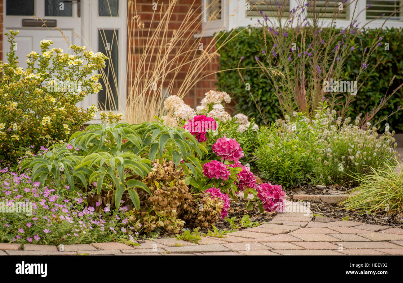 Flower Beds Set Within Block Paving Driveway At Front Of House