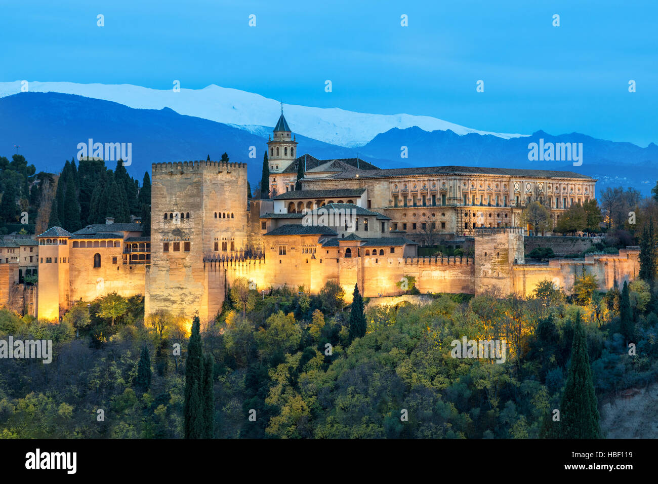 Alhambra - medieval Moorish fortress surrounded by yellow autumn trees illuminated in the evening, Granada, Andalusia, - Stock Image