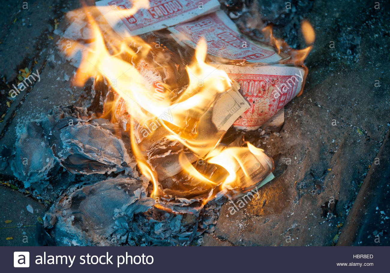 Hanoi Vietnam Fake money, Dong and US dollars is burnt in the gutter at dusk. Burning 'Joss' money is common - Stock Image