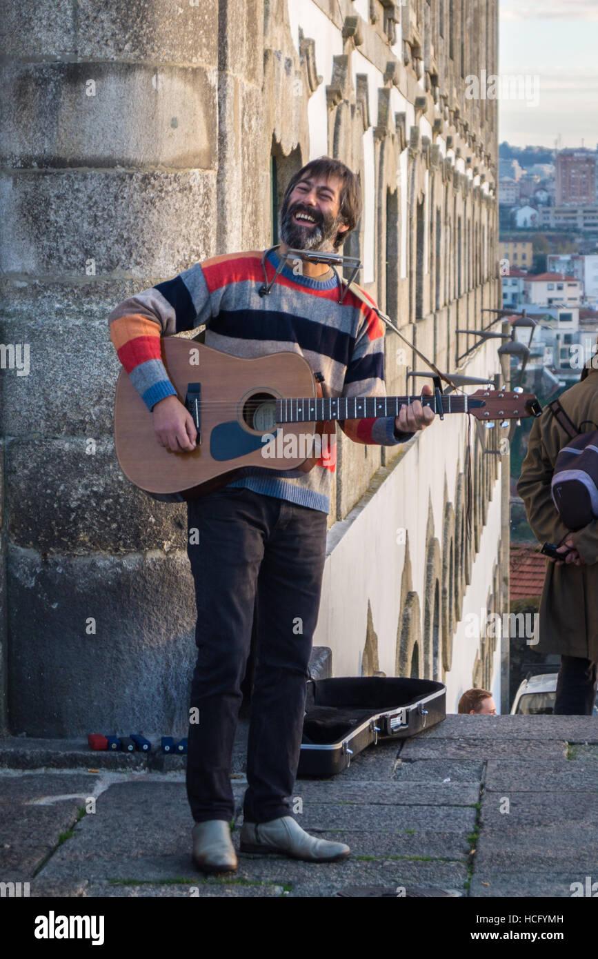 a-busker-playing-a-guitar-terreiro-do-s-porto-portugal-HCFYMH.jpg
