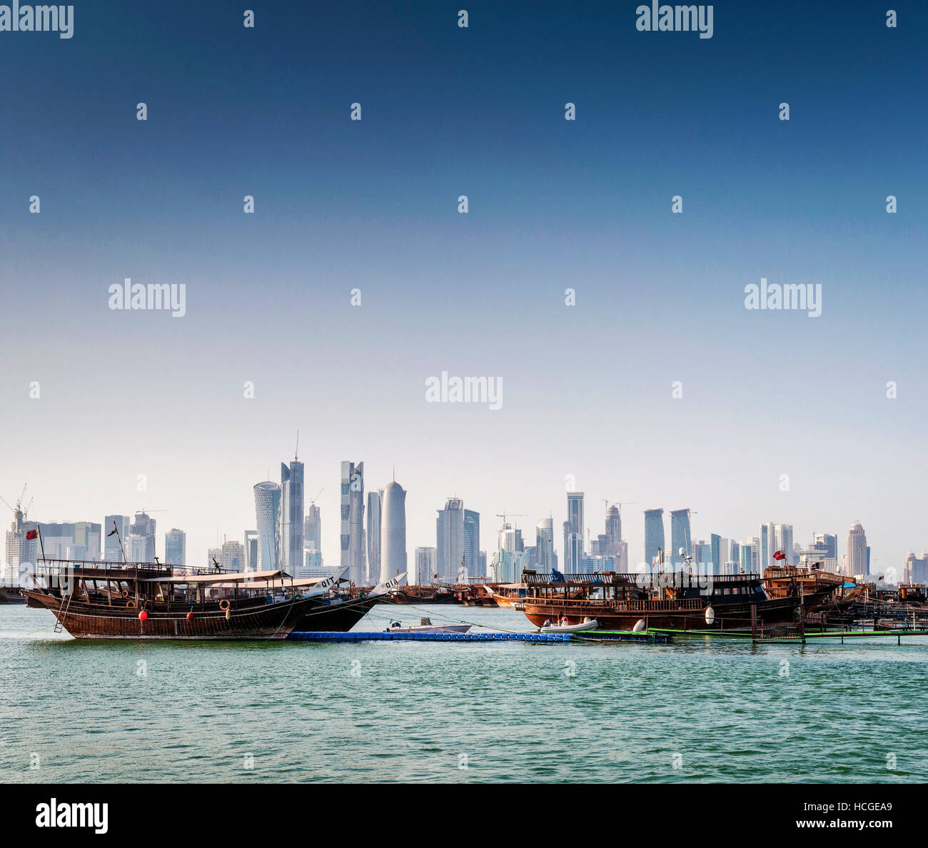 doha city skyscrapers urban skyline view and dhow boat in qatar - Stock Image