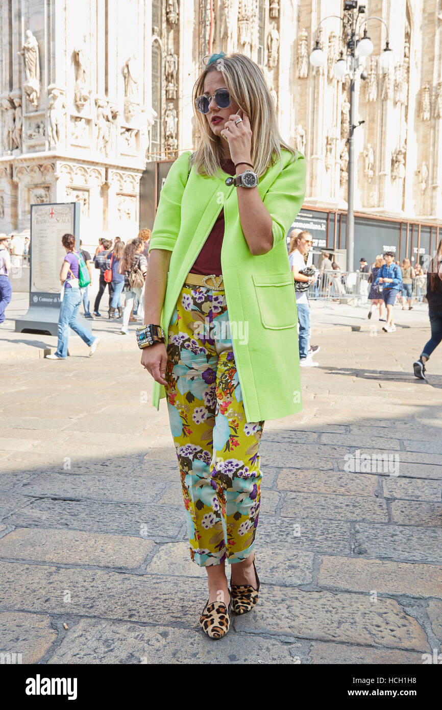 Woman with yellow jacket and trousers with floral pattern before Stella Jean fashion show, Milan Fashion Week street - Stock Image