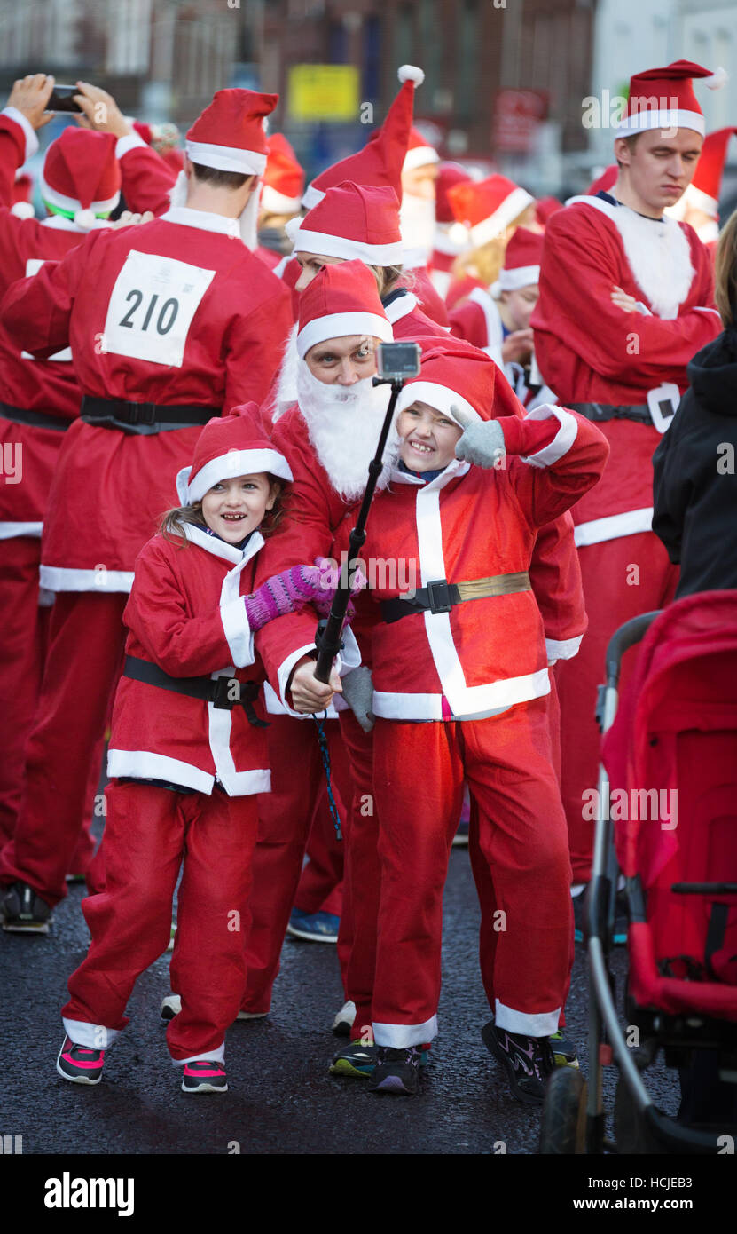 a-family-dressed-as-santas-taking-a-selfie-photo-winchester-hampshire-HCJEB3.jpg