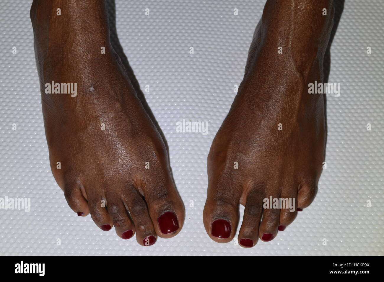 Two out turned female feet with red nail polish on a white ...