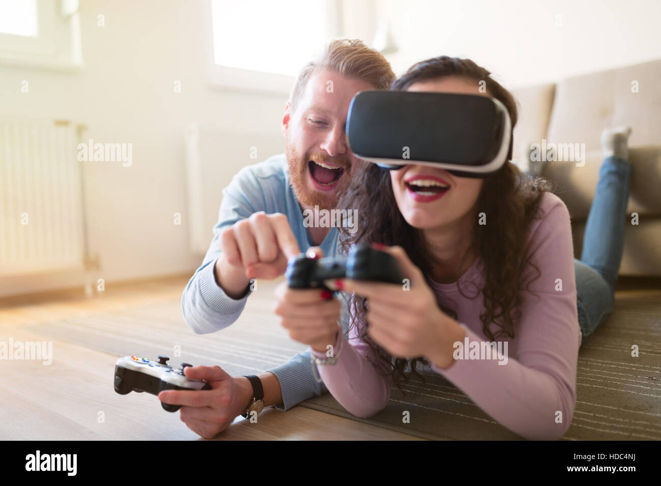 Couple having fun enjoying VR and playing games - Stock Image