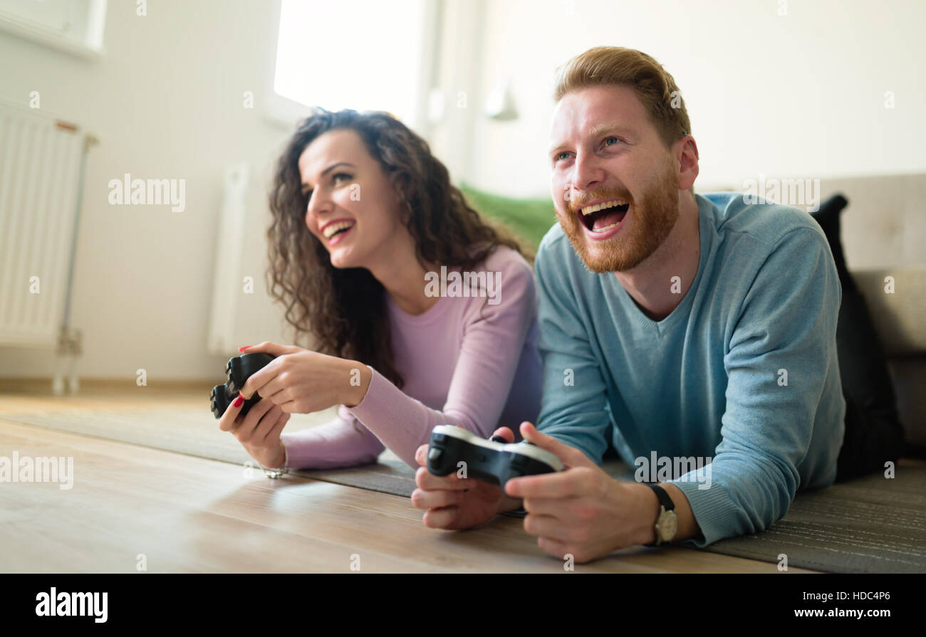 Beautiful couple playing video games on console having fun - Stock Image