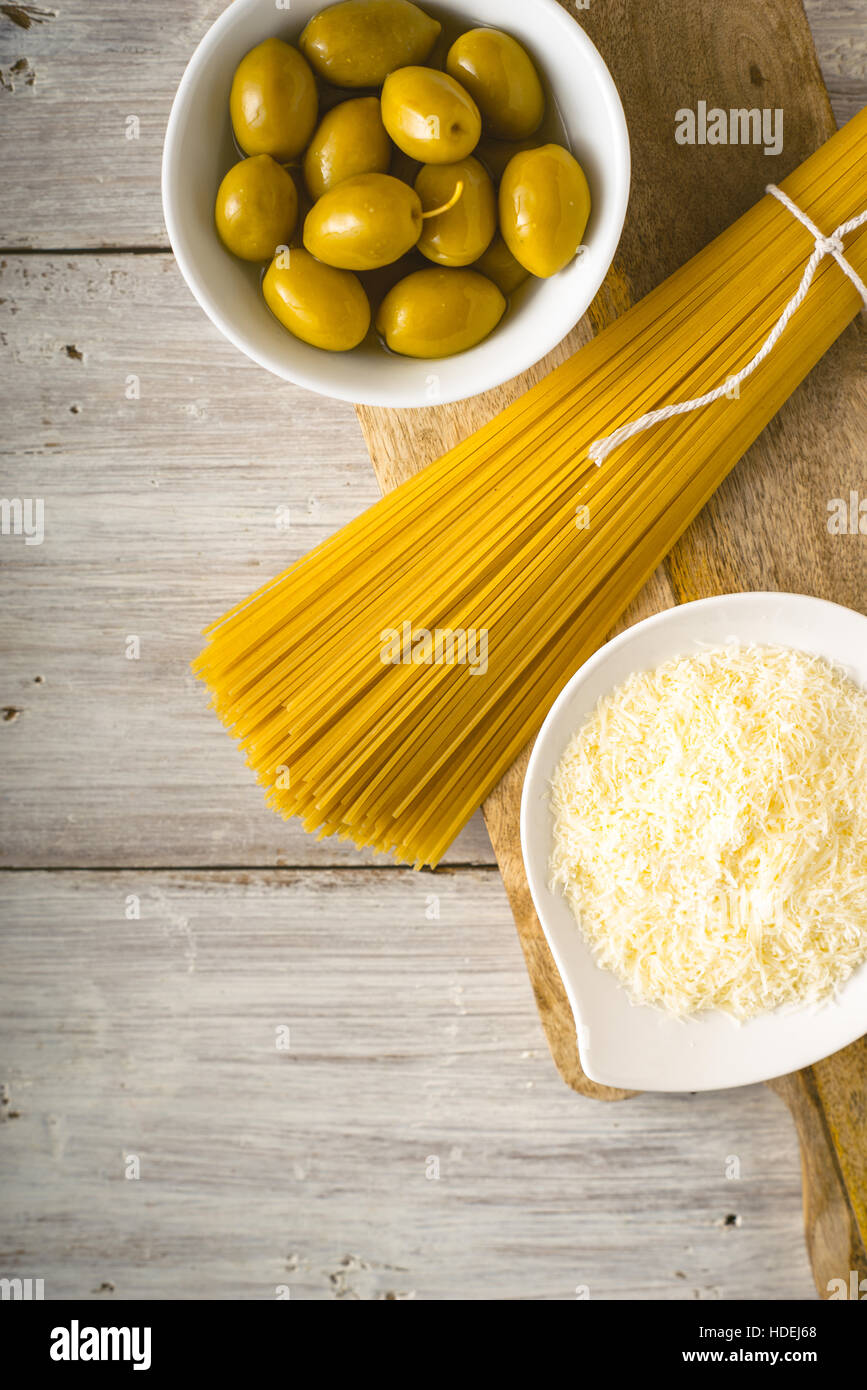 Raw spaghetti with olives and cheese on the white wooden table vertical - Stock Image
