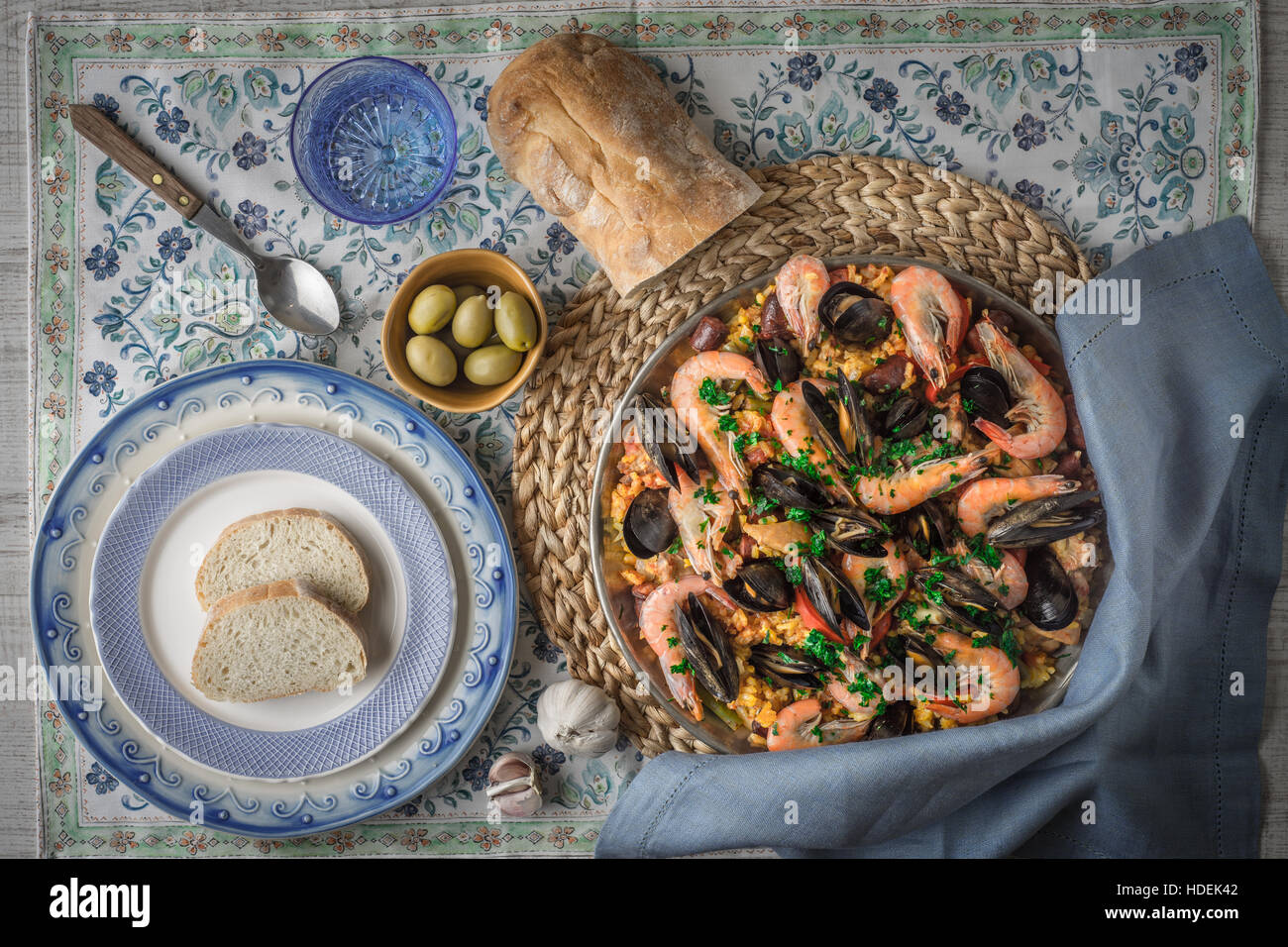 Paella on the metal plate on the beautiful napkin with tableware and bread top view - Stock Image