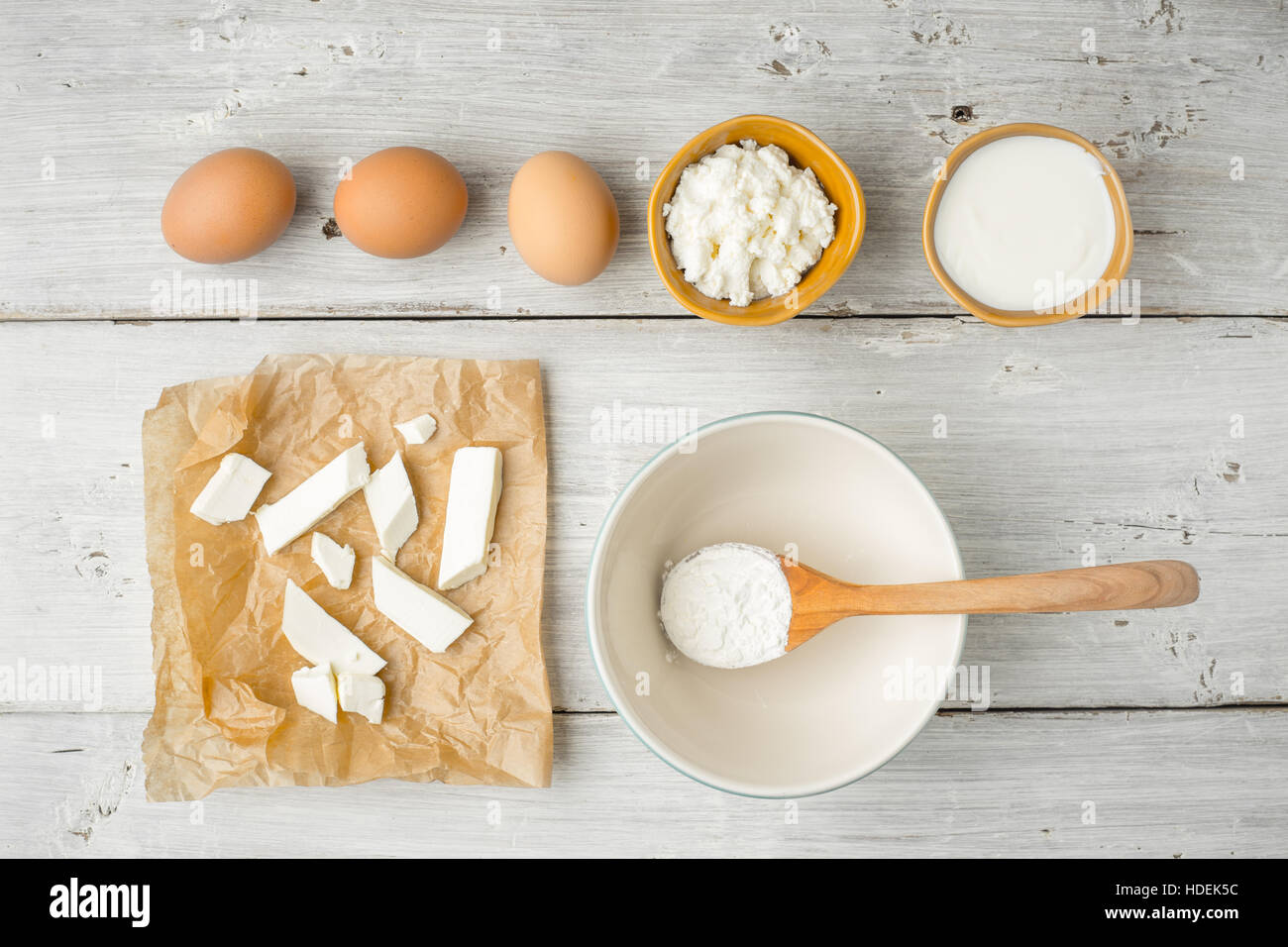 Different fresh cheese with yogurt and eggs on the white wooden table top view - Stock Image