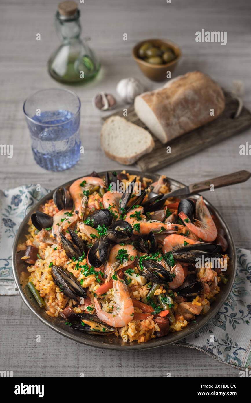 Paella in the metal plate on the wooden table - Stock Image