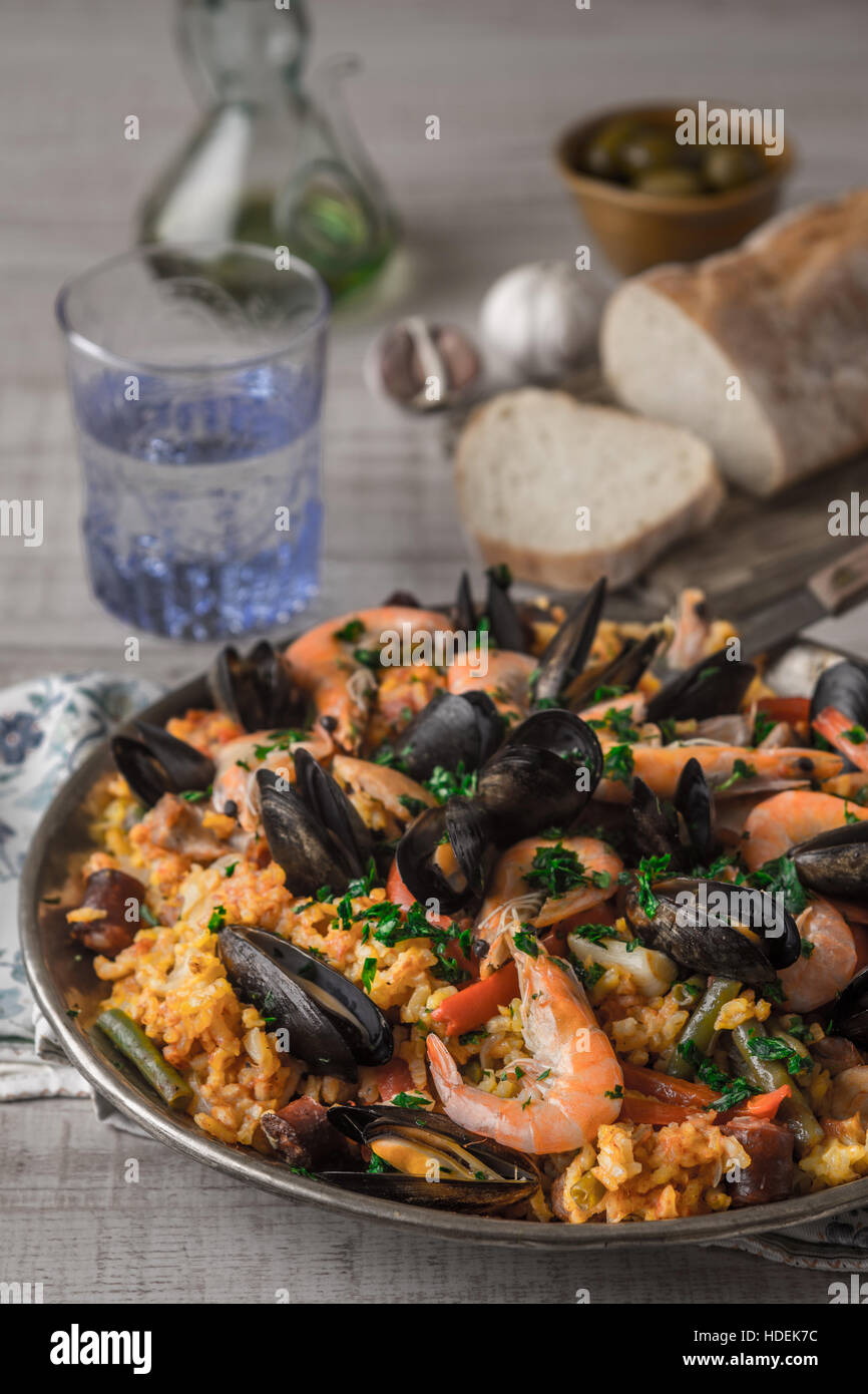 Paella in the metal plate on the wooden table  vertical - Stock Image