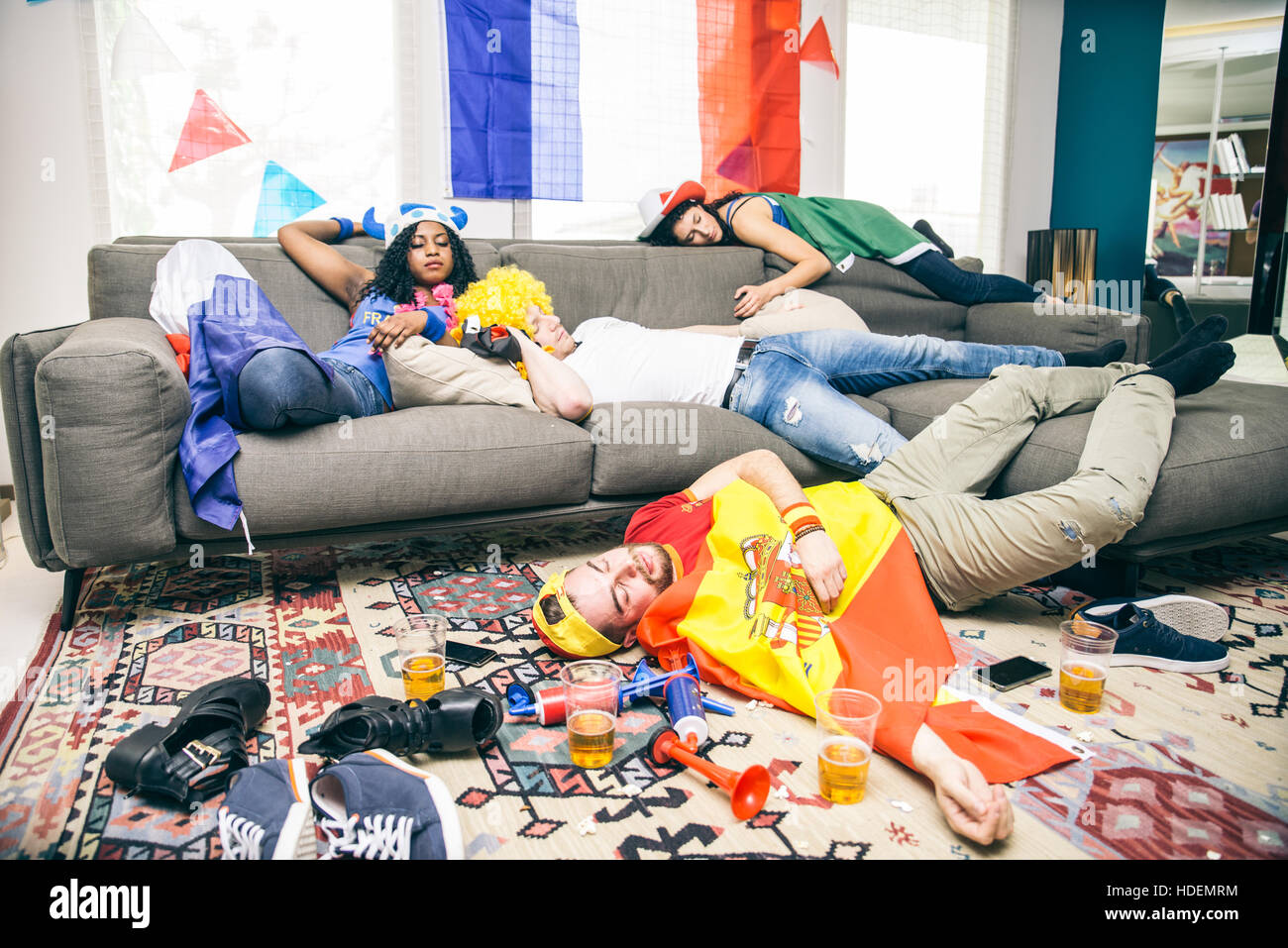 group of friends sleeping in a living room after party drunk stock