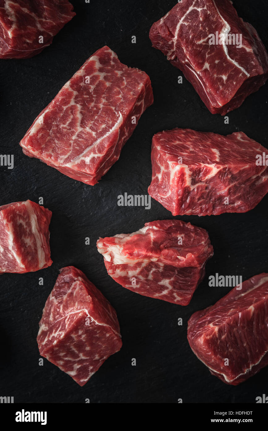 Raw angus beef slices on the black stone  table vertical - Stock Image