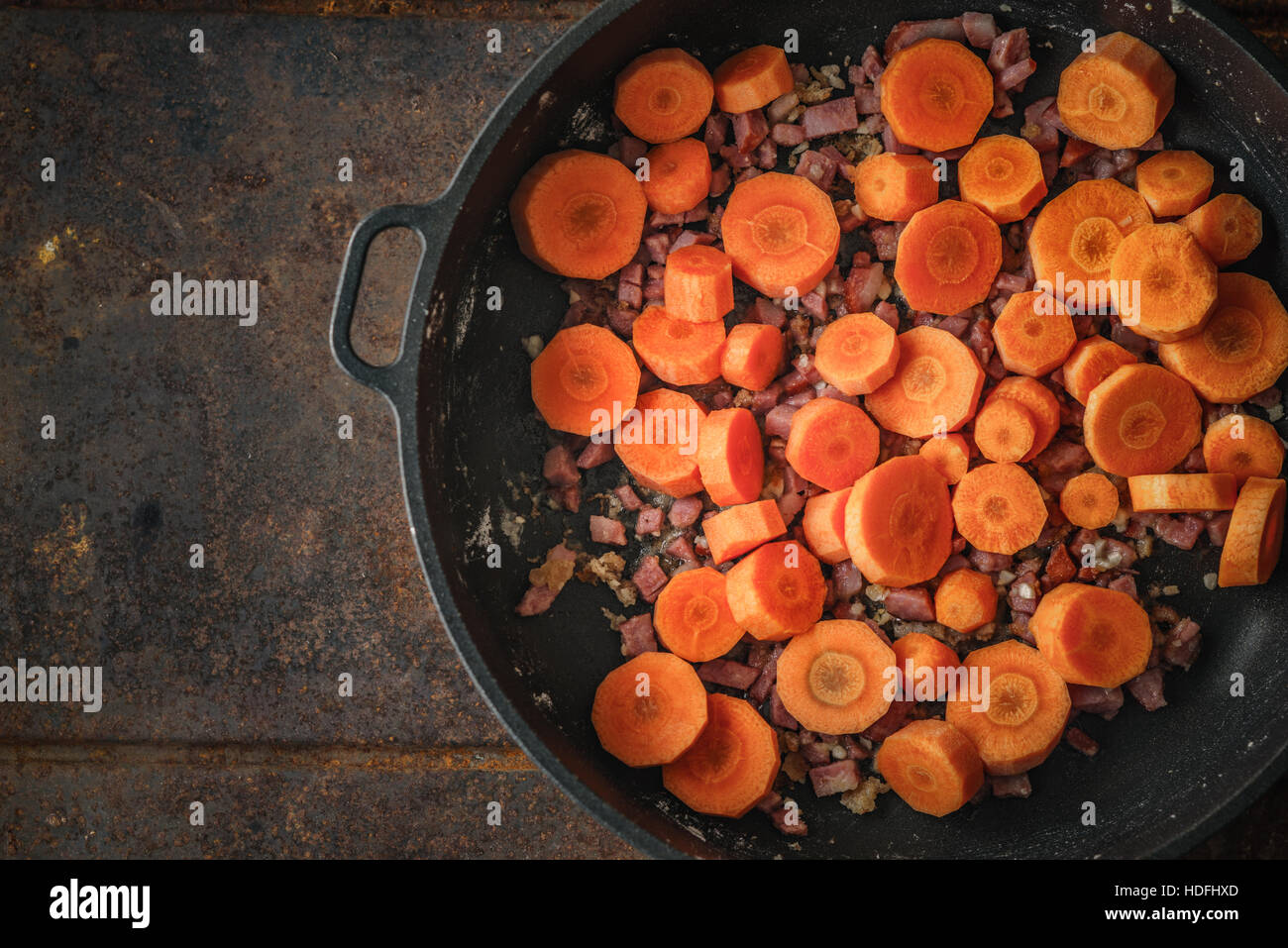 Carrots and bacon in the pan on the metal background - Stock Image