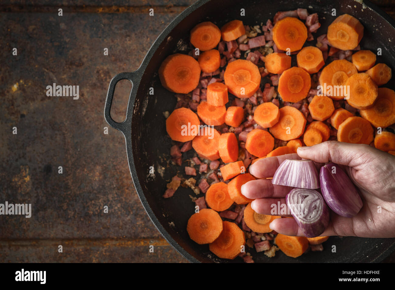 Adding shallot in the pan with bacon and carrots top view - Stock Image