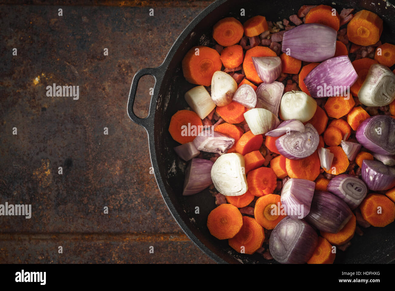 Shallot and carrots in the pan on the metal background - Stock Image