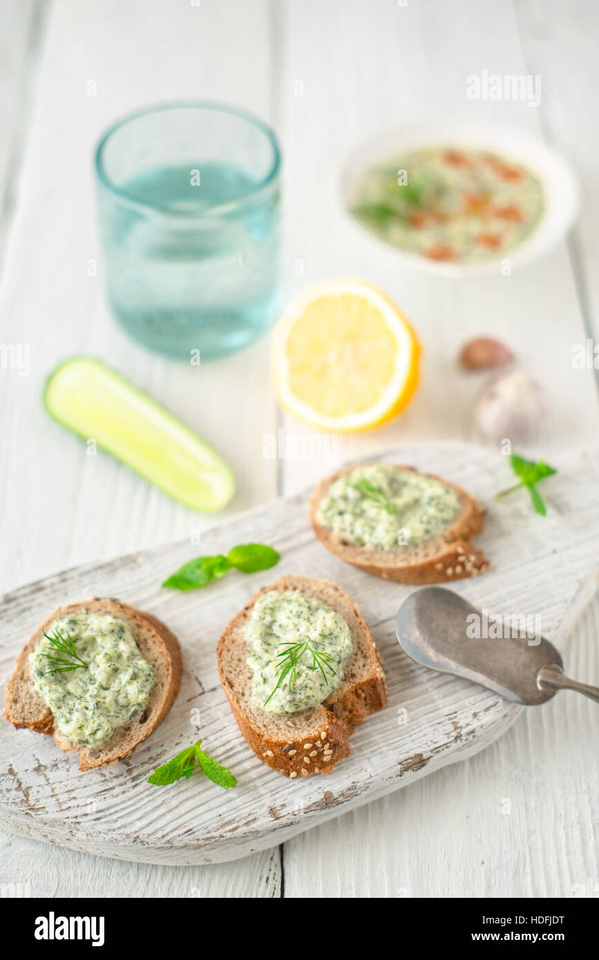 Bread with tzatziki on the white wooden table vertical - Stock Image