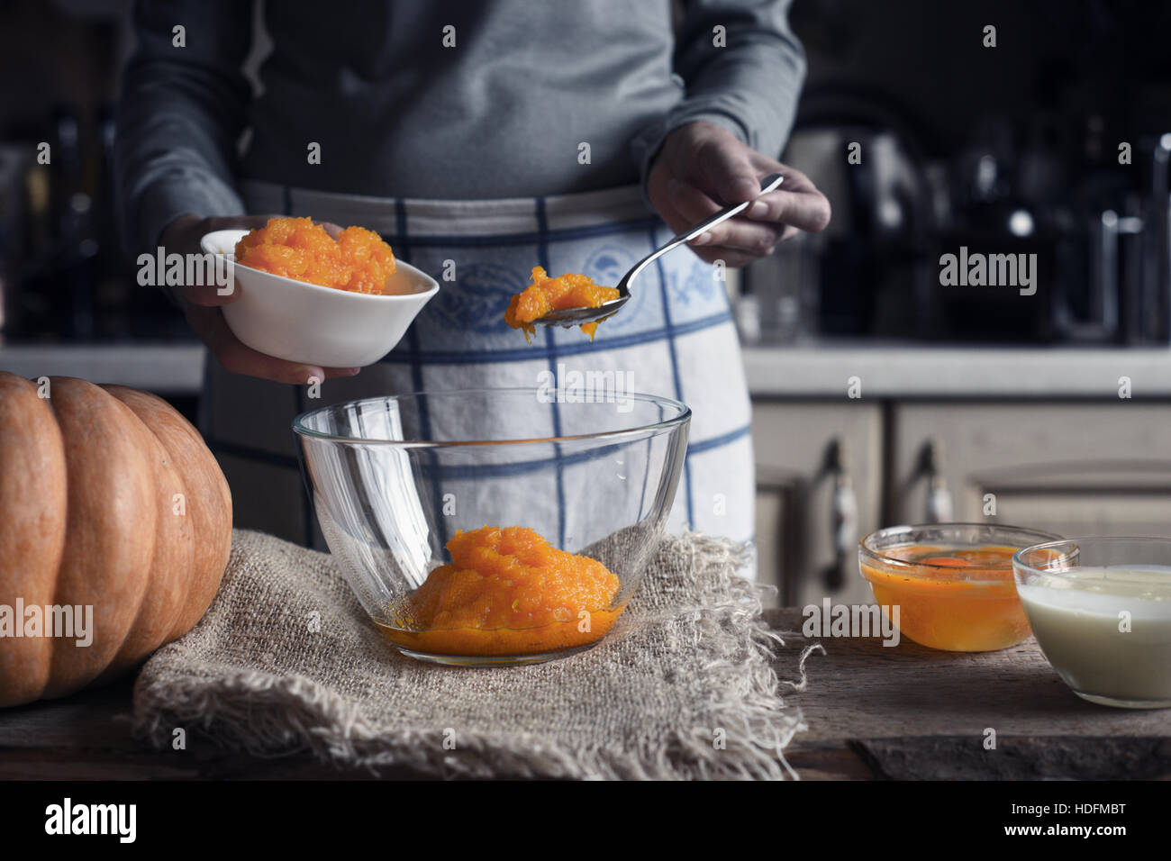 Putting pumpkin puree in the glass bowl - Stock Image