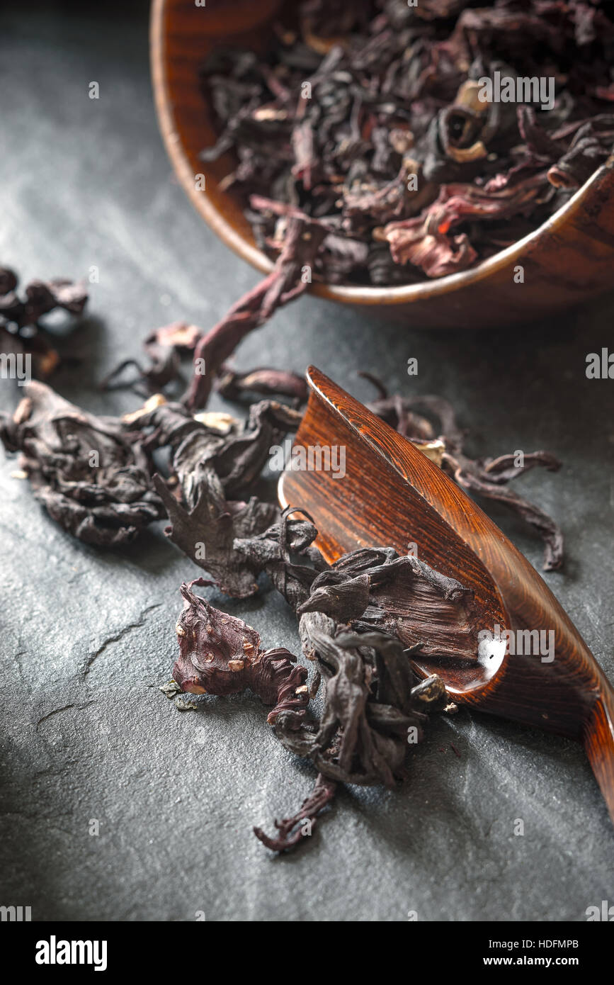 Hibiscus tea in the wooden bowl on the dark stone table vertical - Stock Image