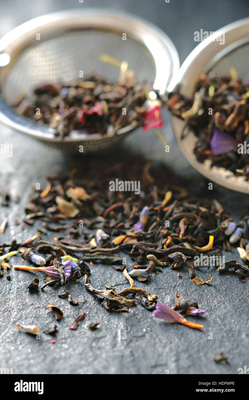 Tea with flower petal in the strainer on the stone background vertical - Stock Image