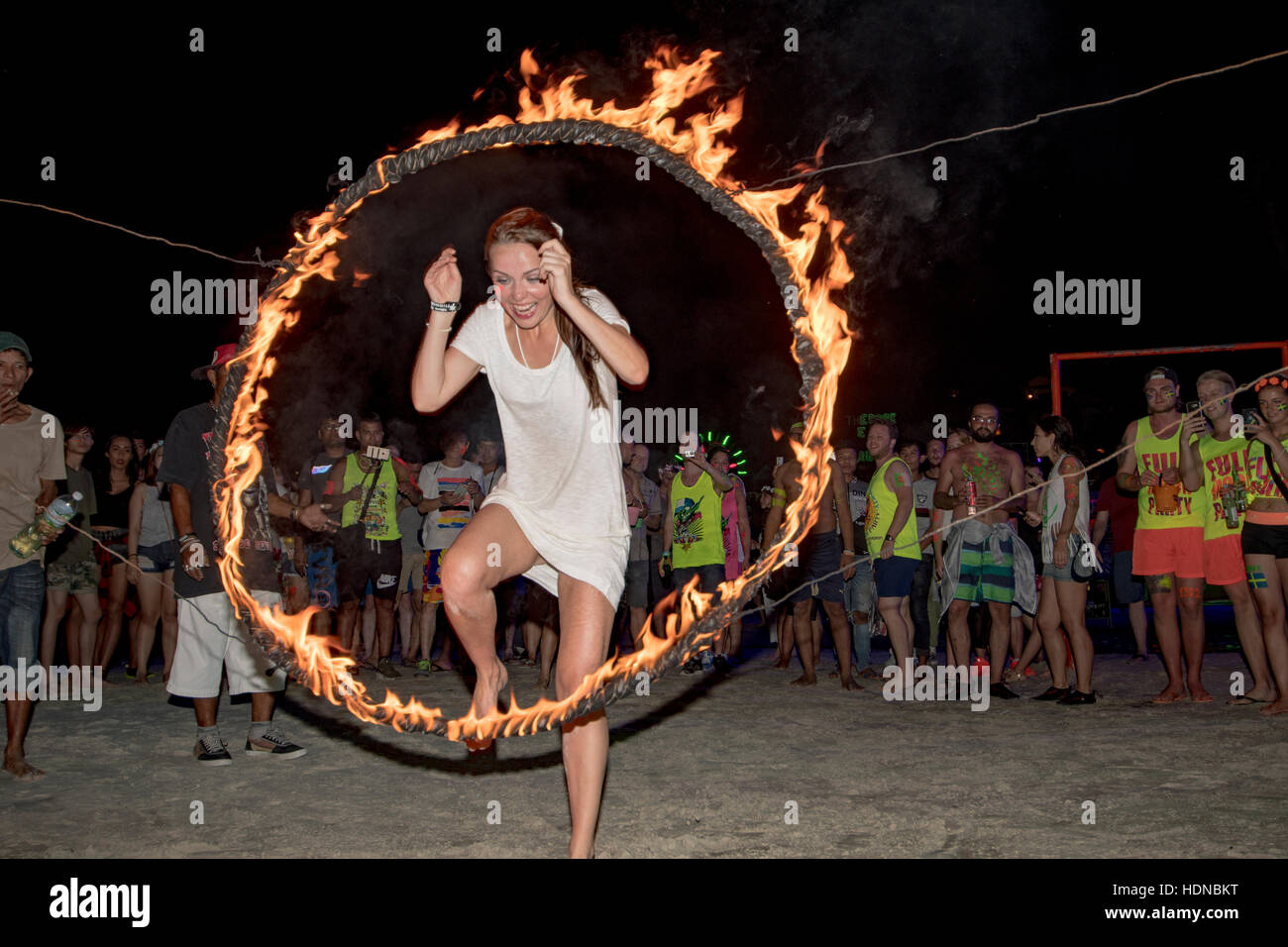Female jumps through a burning hoop at a Full Moon party on Sunrise beach Haad Rin on the island of Kho Phag Nang Stock Photo