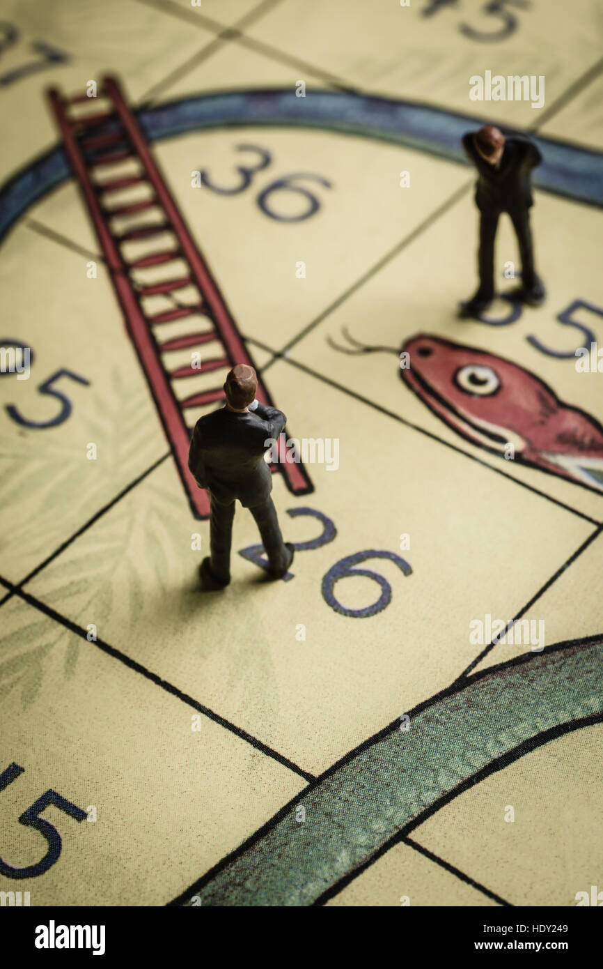 Business men pondering success and failure on a snakes and ladders board a problem solving conceptStock Photo