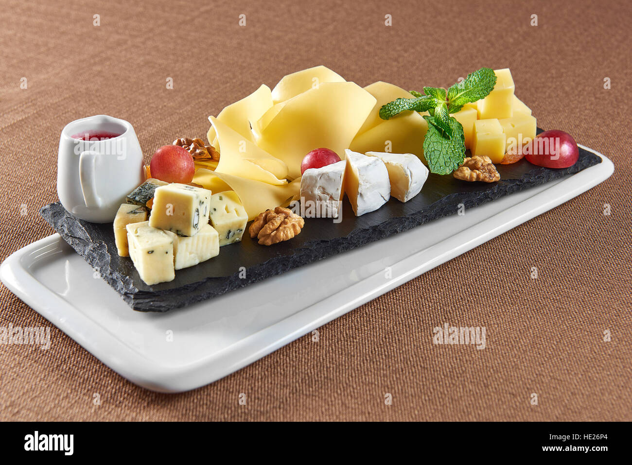 Best cheese in town. Closeup of a delicious cheese plate served with different sorts of cheese grapes walnuts and cranberries jam & Best cheese in town. Closeup of a delicious cheese plate served with ...
