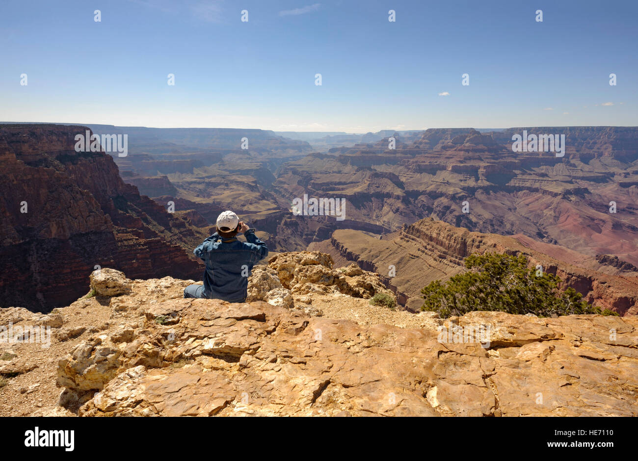 Adventure travel man at edge of the Grand Canyon south rim Pipe Creek Vista taking photo, Arizona USA rear view Stock Photo