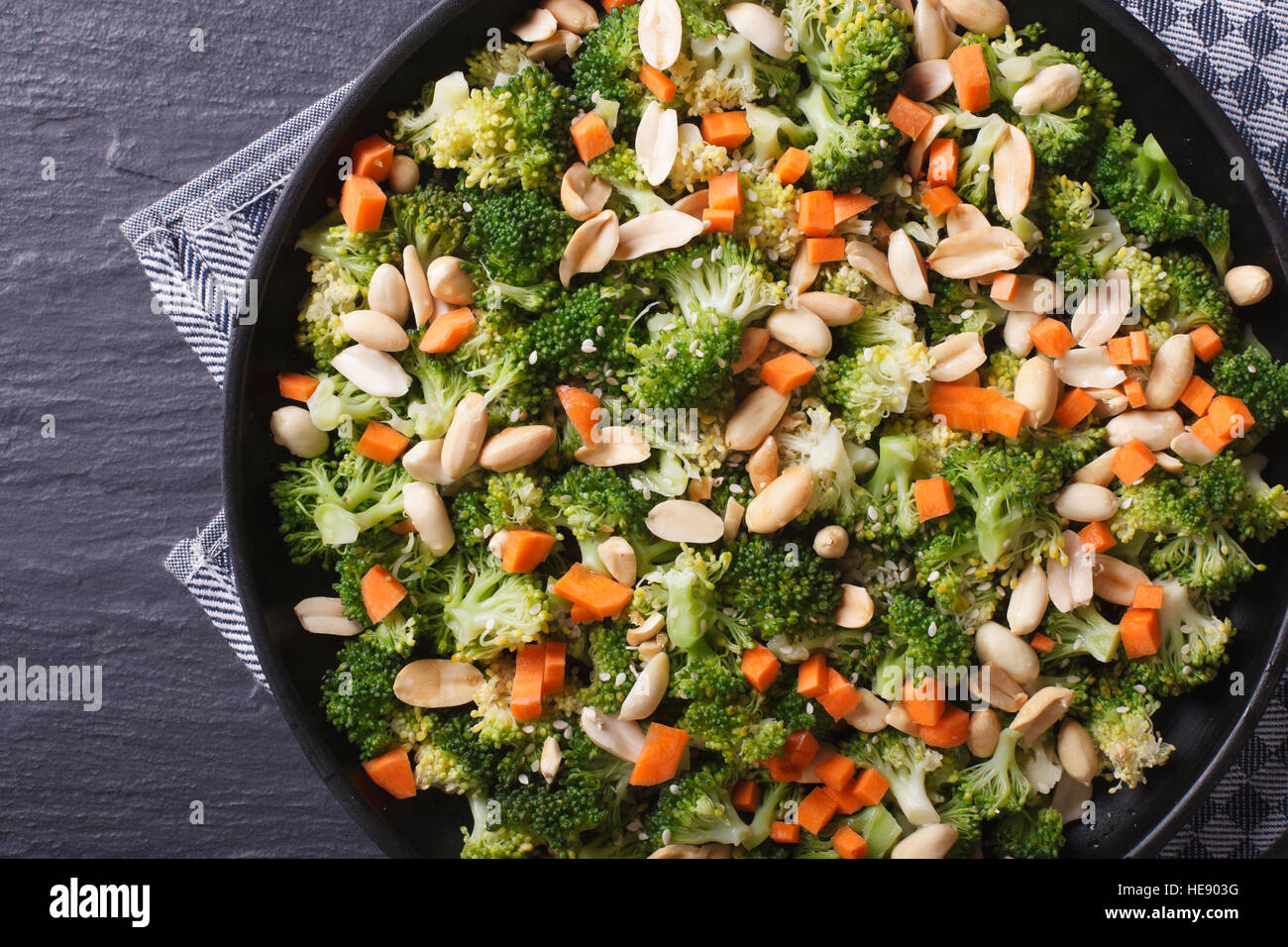 Healthy food: Broccoli with peanuts and carrots close-up on a black plate. horizontal view from above - Stock Image