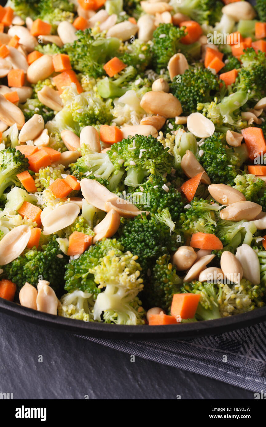 Beautiful salad of broccoli with nuts on a plate macro. vertical - Stock Image
