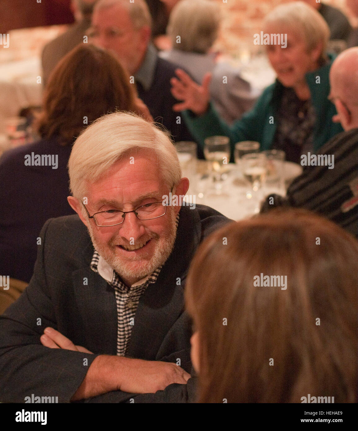 Senior man smiling and looking relaxed at a cafe/café/restaurant table Stock Photo