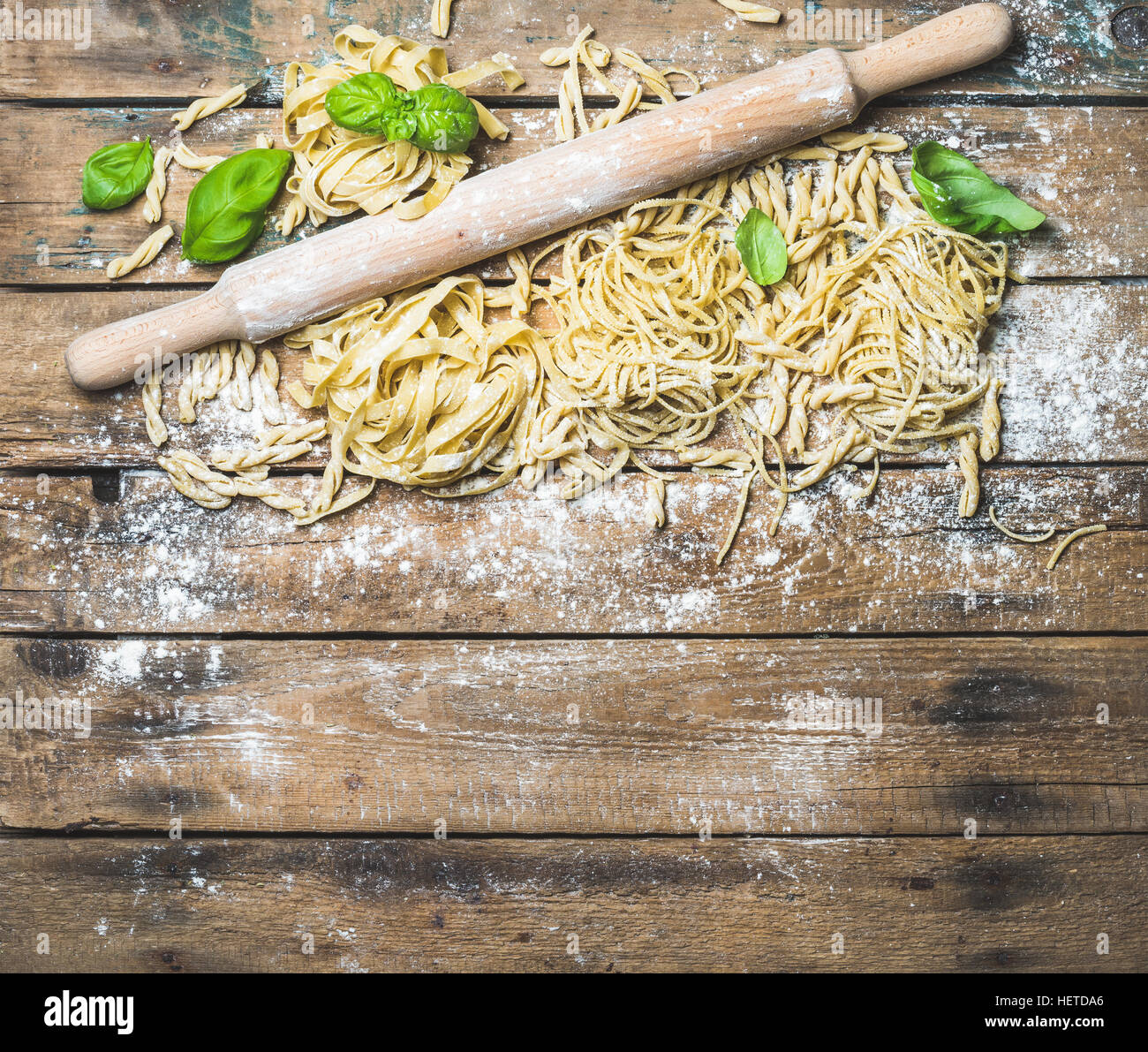 Various homemade fresh uncooked Italian pasta and plunger - Stock Image