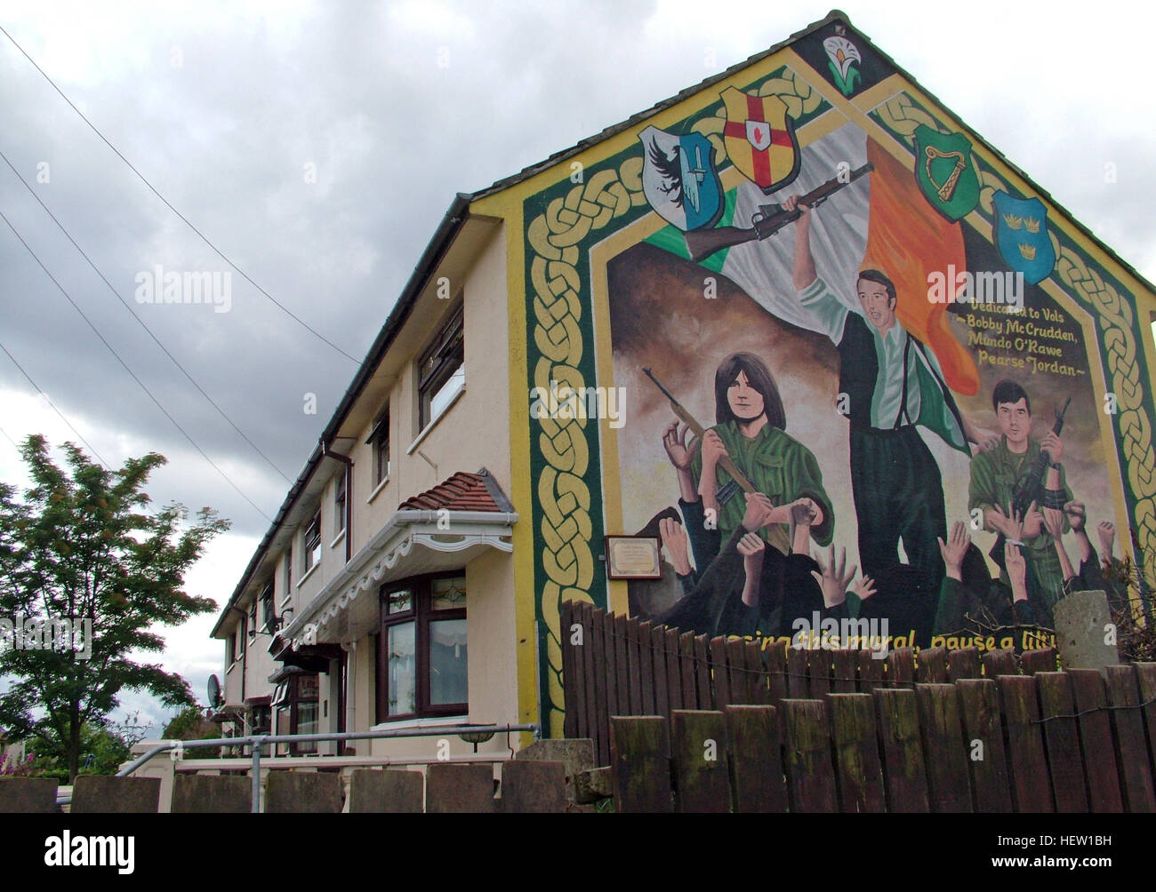 Road,painting,graffiti,resistance,IRA,peace,Northern Ireland,NI,UK,St,street,Eire,Irish,Republic,Irish Republic,conflict,Irish Republican Army,Political Change,on,council,house,gable end,Dedicated,to,Bobby McCrudden,Mundo O-Rawe,Pearse Jordan,Mundo ORawe,flag,rifle,gun,guns,GoTonySmith,@HotpixUK,Tony,Smith,UK,GB,Great,Britain,United,Kingdom,Irish,British,Ireland,problem,with,problem with,issue with,NI,Northern,Northern Ireland,Belfast,City,Centre,Art,Artists,the,troubles,The Troubles,Good Friday Agreement,Peace,honour,painting,wall,walls,tribute,republicanism,Fight,Justice,West,Beal,feirste,martyrs,social,tour,tourism,tourists,urban,six,counties,6,backdrop,county,Antrim,occupation,good,Friday,agreement,peace,reconciliation,IRA,terror,terrorists,genocide,Irish volunteers,Irish,volunteers,Belfast streets,catholic,community,catholics,Buy Pictures of,Buy Images Of,Images of,Stock Images,Tony Smith,United Kingdom,Great Britain,British Isles,republican cause,Belfast Catholic Community