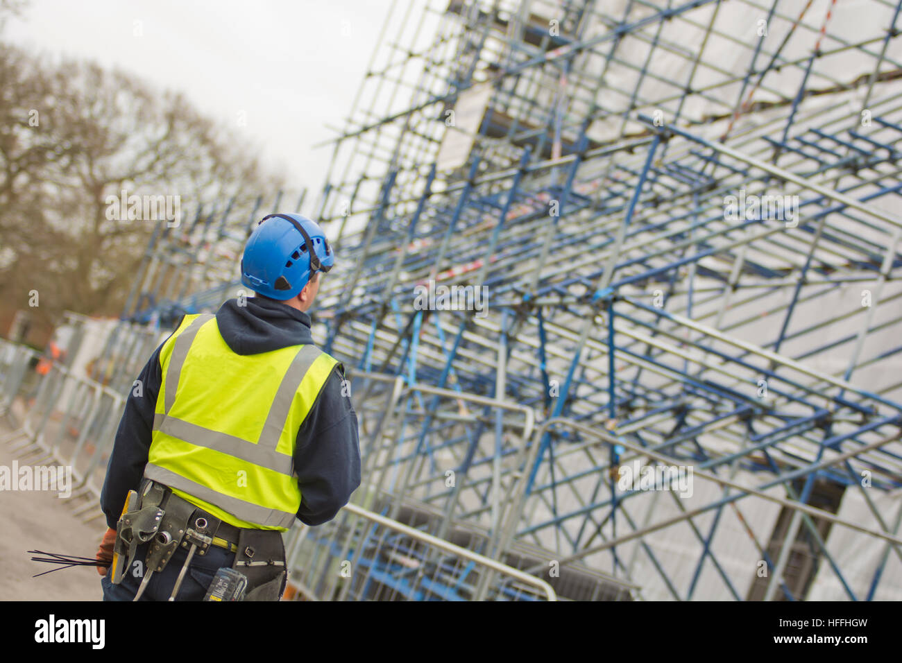 Construction supervisor looks up to scaffolding works at industrial construction site - Stock Image