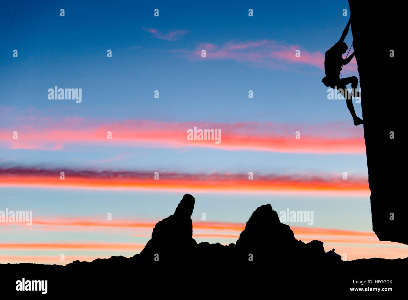Male climber dangles from a sheer rock spire. - Stock Image