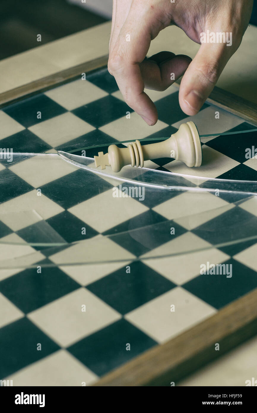 Human hand and the white king in chess - Stock Image